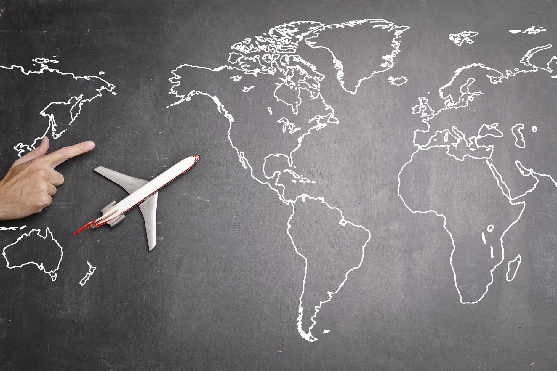 airplane over world map on blackboard